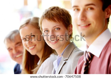 Group of happy successful people in line with focus on woman - stock photo