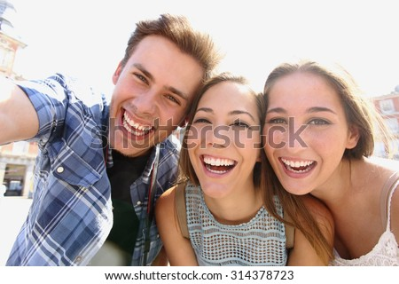 Group of happy teen friends laughing and taking a selfie in the street - stock photo