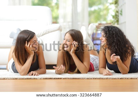 Group of happy teen friends talking lying on the floor at home - stock photo
