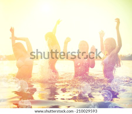Group of happy teen girls playing in water at the beach on sunset. Beauty and joyful teenager friends having fun, dancing and spraying over summer sunset. Beach party. Sun flare. - stock photo