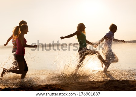 Group of happy teenagers running through the water at the beach - stock photo