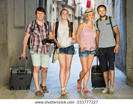 Group of happy travelers walking at the street with luggage - stock photo