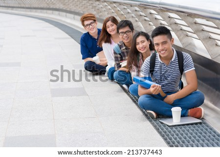 Group of happy Vietnamese students sitting in a row outdoors - stock photo