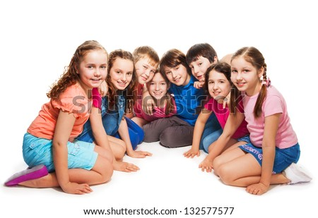 Group of happy 10 years old boys and girls sitting together in semi-circle - stock photo