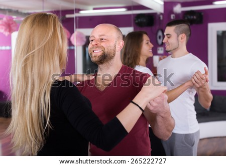 Group of happy young adults dancing salsa in club - stock photo