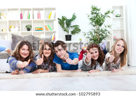 Group of happy young boy and girls lying down and holding thumbs up in the air - stock photo