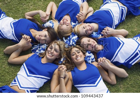 Group of happy young cheerleaders lying on field forming a circle - stock photo
