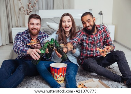 Group of happy young friends drinking beer and eating pizza at home - stock photo