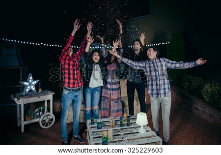 Group of happy young friends raising their arms and having fun among the colorful confetti in a outdoors party. Friendship and celebrations concept. - stock photo