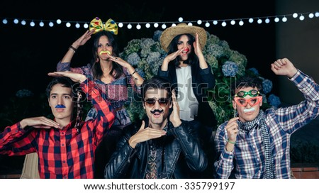 Group of happy young friends with costumes having fun in outdoors party. Friendship and celebrations concept. - stock photo