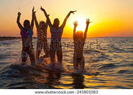 Group of happy young girls jumping at the beach on beautiful summer sunset, motion blur - stock photo