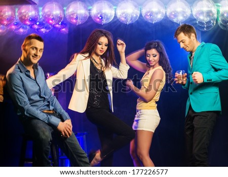 Group of happy young people dancing at night club  - stock photo