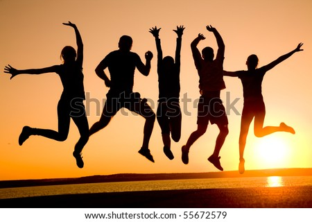 group of happy young people dancing at the beach on  beautiful summer sunset - stock photo