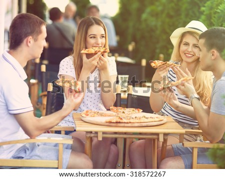 Group of happy young people eating pizza in a restaurant - stock photo