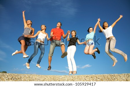 group of happy young people jumping at the beach on  beautiful summer day - stock photo