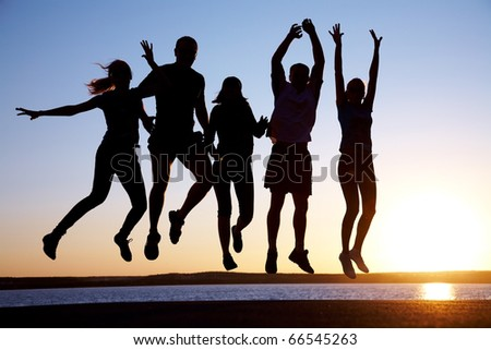 group of happy young people jumping at the beach on beautiful summer sunset - stock photo