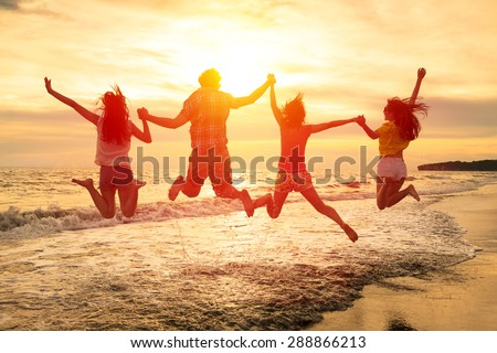 group of happy young people jumping on the beach - stock photo
