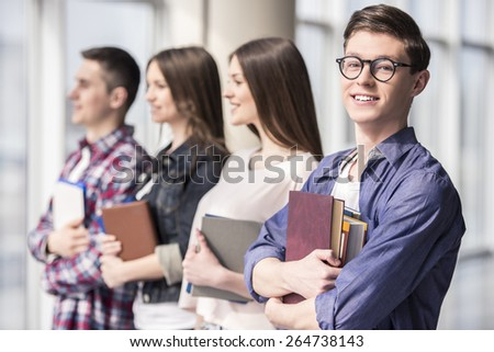 Group of happy young students in a college. - stock photo