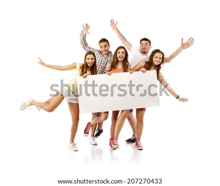 Group of happy young teenager students standing and smiling with blank placard board isolated on white background. - stock photo
