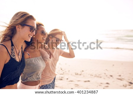 Group of happy young women walking on a beach. Three female friends strolling along the sea shore on a summer day, enjoying vacation. - stock photo