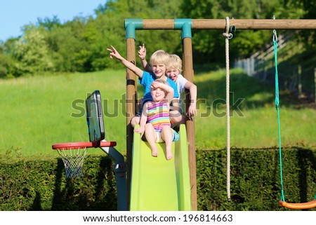 Group of healthy happy kids, two active school boys and funny toddler girl, playing together outdoors on the slide at the backyard of the house in the garden with beautiful field view - stock photo