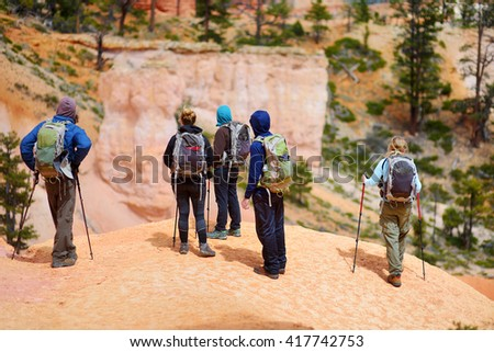 Group of hikers admiring a view of red sandstone hoodoos in Bryce Canyon National Park in Utah, USA - stock photo