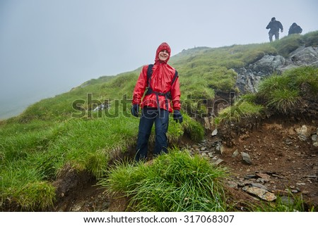 Group of hikers descending on a mountain with raincoats during rain - stock photo