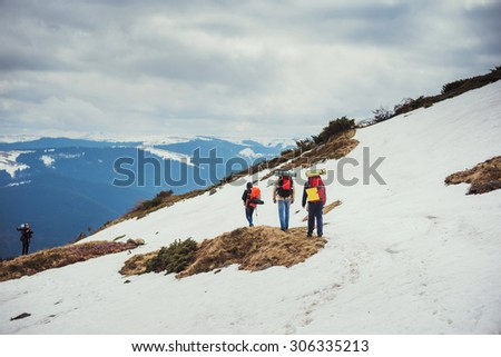 group of hikers hiking in the mountains in snow with backpacks - stock photo