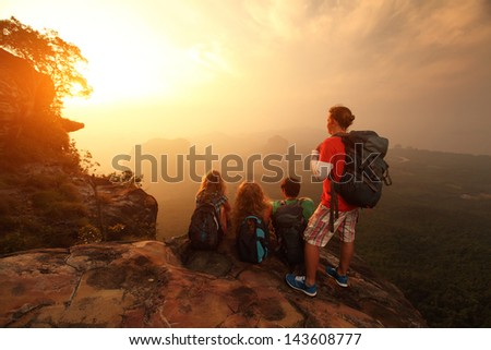 Group of hikers relaxing on top of a mountain and enjoying sunrise - stock photo