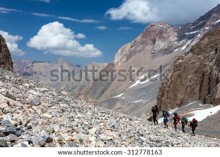 Group of Hikers Walking on Deserted Rocky Terrain Large Group of People Sport Clothing Going Heavy Load Backpacks Climbing Gear Up Mountain Peaks Sunlight Blue Sky Majestic Summits Background - stock photo