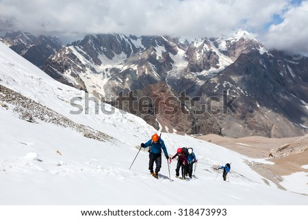 Group of Hikers Walking on Snow and Ice Terrain Large Group of People Sport Clothing Going Heavy Load Backpacks Climbing Gear Up Mountain Peaks Sunlight Cloud Sky Summits Background - stock photo