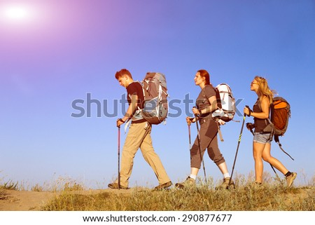 Group of hikers walks on grassy lawn. Three people two female one female heavy loaded with backpacks go across grassy terrain blue sky and sun on background - stock photo