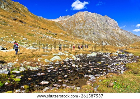 Group of hiking tourists goes along a small mountain river. Picture was taken during trekking hike in scenic Caucasus mountains at autumn, Arhiz region,Abishira-Ahuba range, Karachay-Cherkessia,Russia - stock photo