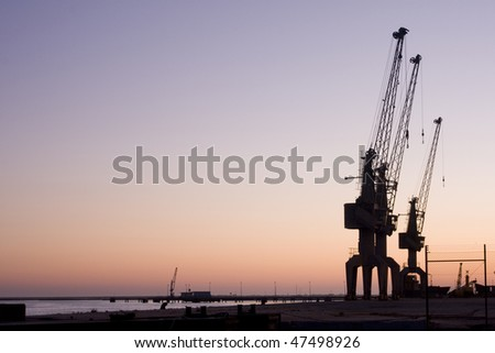 Group of huge sky cranes at a construction site at sunset, silhouette against orange sky - stock photo