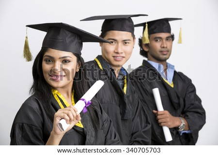 Group of Indian college graduates wearing cap and gown holding diploma on white background - stock photo