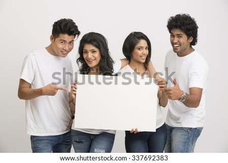 Group of Indian young people holding blank white board on white background. - stock photo