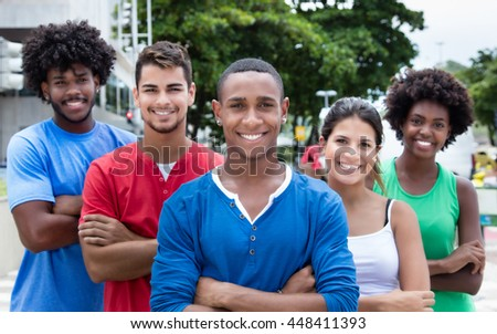 Group of international young adults laughing at camera in city - stock photo