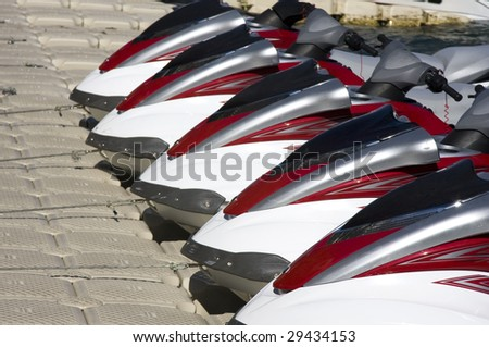 Group of Jet Skis on Dock for Fun - stock photo