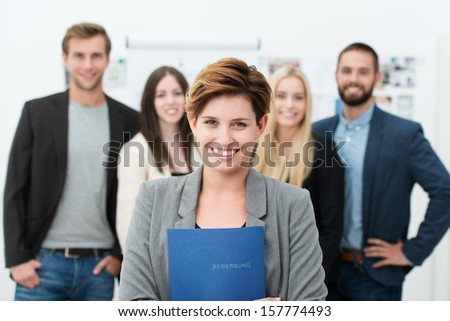 Group of job applicants with a smiling confident young woman in the foreground holding her Curriculum vitae in her hands - stock photo
