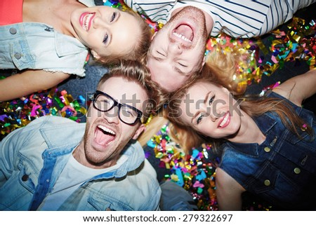 Group of joyful friends lying on the floor in nightclub - stock photo