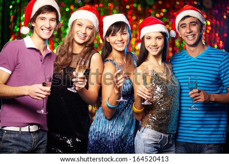 Group of joyful friends toasting at xmas party - stock photo