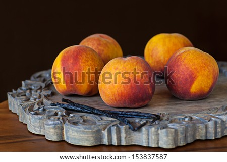 Group Of Juicy Farm Fresh Whole Ripe Peaches With Vanilla Bean Pods On A Decorative Wooden Breakfast Or Lunch Platter And A Dark Chocolate Brown Background Wallpaper Background - stock photo