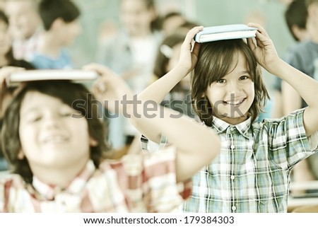 Group of kids at school room having fun time holding books on heads - stock photo