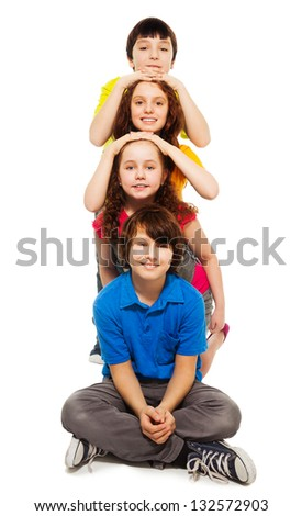 Group of kids laying their head on top of each others, smiling, isolated on white - stock photo