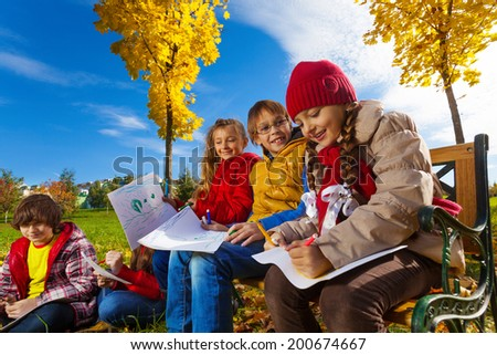 Group of kids sitting on the bench in the park under the autumn maple trees and drawing images - stock photo