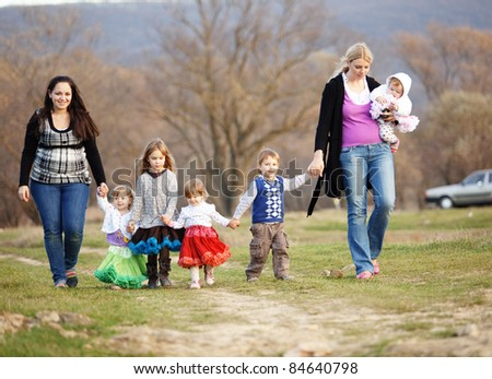 Group of kids with parents walking outdoors - stock photo