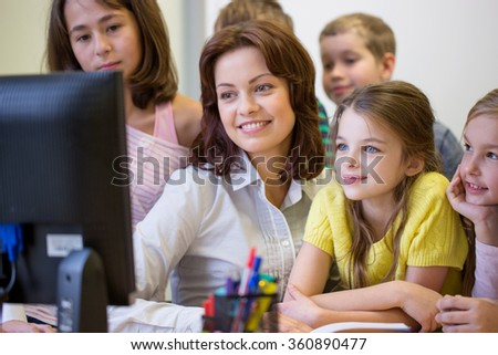group of kids with teacher and computer at school - stock photo