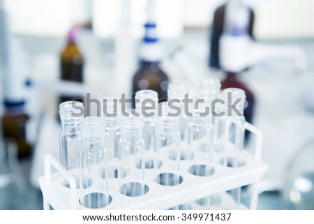 Group of laboratory flasks with a clear liquid on desk in laboratory interior. - stock photo