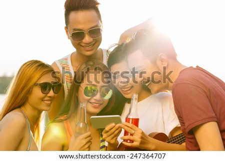 Group of laughing young people watching funny video or photo on the smartphone - stock photo