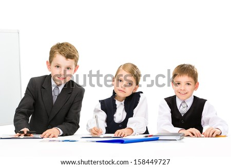 Group of little business people sitting at the table, isolated. Concept of teamwork and cooperation - stock photo